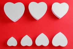 Handmade cardboard hearts on a red background. The concept is suitable for love stories and for Valentine`s Day.  stock photos