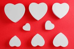 Handmade cardboard hearts on a red background. The concept is suitable for love stories and for Valentine`s Day.  royalty free stock photo