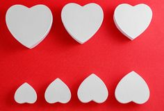 Handmade cardboard hearts on a red background. The concept is suitable for love stories and for Valentine`s Day.  royalty free stock photography