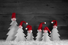 Handmade carved christmas trees with red santa hats on wooden ol Stock Images
