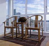 Handmade carved wooden chairs. Carved wooden chairs in a floor to ceiling modern bay window and city views Stock Photo