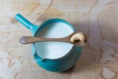 Handmade ceramiczny miotacz nerkodrzewu mleko ześrodkowywał, rocznika drewniany tło, drewniana łyżka z pojedynczym nerkodrzewem zdjęcie stock