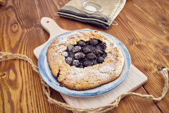 Handmade cherry pie. On a blu dish, on a wooden table. Country style Stock Image