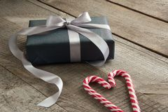 Handmade chistmas present from black wrapping paper, silver ribbon and candy cane in shape of heart on wooden surface. Copyspace. Handmade chistmas present from Stock Photos