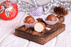 Handmade chocolate coconut candy on wooden table with Christmas royalty free stock image
