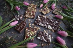 Handmade chocolate with nuts and dried fruits with Pink tulips, Chocolatier, Sweet gifts, Valentine`s Day, White Day, Howaito day. Handmade chocolate with nuts stock image