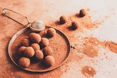 Handmade chocolate truffle on a plate. Dark chocolate candies in cocoa powder on a dark brown background. Flat layout. royalty free stock image