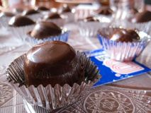 Handmade chocolate truffles in silver wrappers on tray Stock Photos