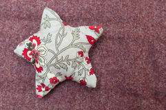 Handmade christmas decoration, Star made of fabric. On fabric background Stock Photo