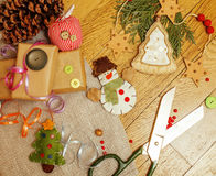 Handmade christmas gifts in mess with toys, candles, fir, ribbon, tree cone wooden vintage, post card view Stock Photo