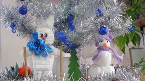 Handmade Christmas toys under Christmas tree hare and snowman. Silver Christmas tree in the children`s room is decorated stock footage