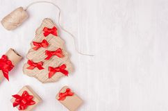 Handmade christmas tree of natural jute decorated of red bows and gift boxes on soft white wood board, top view, copy space. stock image