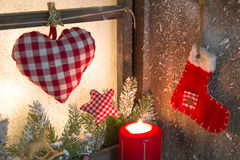 Handmade Christmas wooden window decoration with heart and a red santa boot stock photos