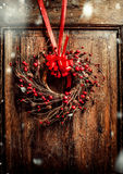 Handmade Christmas wreath hanging on aged old wooden door with red ribbon and berries with snow Royalty Free Stock Photography