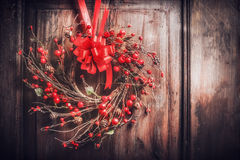 Handmade Christmas wreath hanging on dark wooden door with red ribbon and berries , front view, retro Stock Images