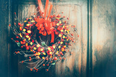 Handmade Christmas wreath hanging on wooden door with red ribbon , berries and bokeh lighting, front view, retro styled Stock Image
