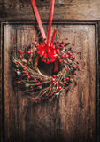 Handmade Christmas wreath hanging on wooden door with red ribbon and berries. Front view Royalty Free Stock Photos