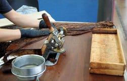 Handmade cigar preparation with big tobacco leaves stock photos