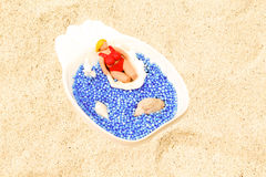 Handmade clay model on shell. Beach scene with artificial water and natural coral sand. Fat tourist in red bikini swim in sea. Summer vacation for puppet Royalty Free Stock Photos