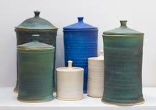 Handmade clay pottery set. On a white shelf royalty free stock photos