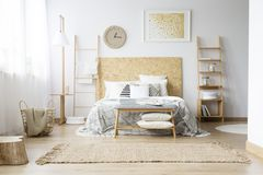 Handmade clock in bohemian bedroom. Gold painting and handmade clock in bohemian bedroom with king-size bed and wooden furniture stock image