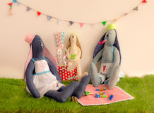 Handmade cloth rabbit dolls sitting on the grass and celebrating. In party concept Royalty Free Stock Image