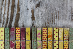 Handmade clothespins in a wood background Stock Images