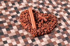 Handmade coffee heart. Handmade heart made of coffee beans on checked napkin. Cinnamon stick and star anise Royalty Free Stock Images