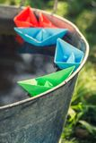 Handmade color paper boats quietly floating on water stock photography