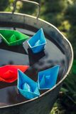 Handmade color paper boats on water as travel concept stock photo