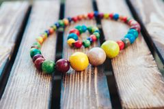 Handmade Colored Jewelry. Colored beads and wood bracelet. Wooden background royalty free stock photo