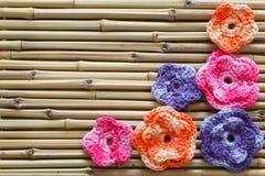 Handmade colorful crochet flowers on bamboo Stock Photos