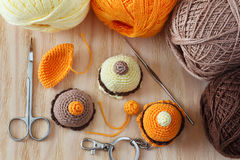 Handmade colorful crochet toys sweets. Making of handmade colorful crochet toys sweets (key ring) with skein on wooden table. Selective focus Royalty Free Stock Images