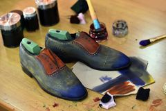 Handmade colorful luxury man shoes are hand-painted in a production factory. royalty free stock photos