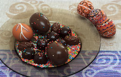 Handmade colorful painted easter egg with chocolate candies and eggs against matching tablecloth Stock Images