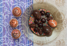 Handmade colorful painted easter egg with chocolate candies and eggs against matching tablecloth Royalty Free Stock Images