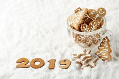 Handmade cookies in a glass cup and text 2019 from wooden figure on white winter snow background with copy space. Top view. Horizontal view. New Year and royalty free stock photos