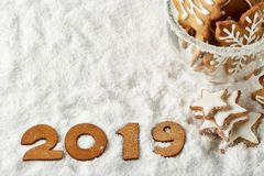 Handmade cookies in a glass cup and text 2019 from wooden figure on white winter snow background with copy space. Top view. Horizontal view. New Year and stock image