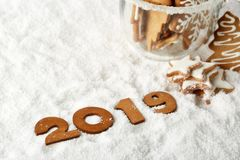 Handmade cookies in a glass cup and text 2019 from wooden figure on white winter snow background with copy space. Top view. Horizontal view. New Year and royalty free stock images