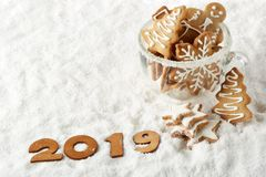 Handmade cookies in a glass cup and text 2019 from wooden figure on white winter snow background with copy space. Top view. Horizontal view. New Year and royalty free stock photo