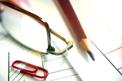 Handmade copy, red clip, pencil, glasses on black. Brightly lit by highlighting, working on a document. Glasses on black stock photography
