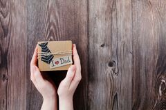 Free Handmade Craft Box Gifts With Paper Tie, Text I Love Dad In Hands On Wooden Background. Concept International Father`s Day, Stock Image - 216322311