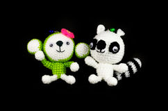 Handmade crochet monkey and Raccoon doll on black background royalty free stock photography