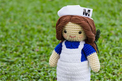 Handmade crochet nurse doll. In the grass Stock Image