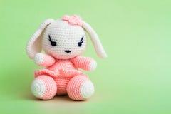 Handmade Crochet Rabbit Toy on Green Background. Stock Photo