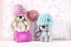 Handmade crochet rabbit toys on green background. Amigurumi doll. Stock Images