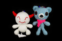 Handmade crochet white devil and dog doll on black background Royalty Free Stock Photos