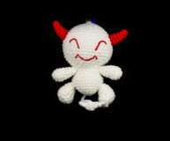 Handmade crochet white devil with red ear doll on black backgrou Royalty Free Stock Images