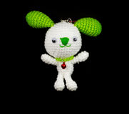 Handmade crochet white rabbit with green ear doll on black backg Stock Photo