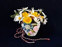 Handmade crocheted basket with spring flowers and red and white string, known as Martisor. Handmade crocheted basket with spring flowers and red and white stock photography
